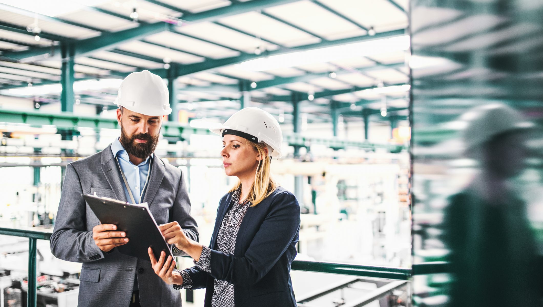 A portrait of a serious mature industrial man and woman engineer with clipboard in a factory, talking.